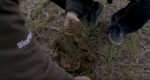 Close up of two people kneeling with soil